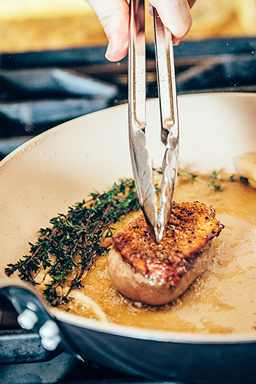 Matfer All Purpose Stainless Steel Tongs in the hands of Chef Derrick Peltz as he creates a delicous duck dish.